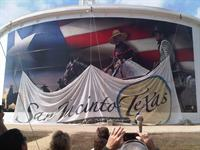 San Jacinto, Texas cowboys in front of Texas flag artwork