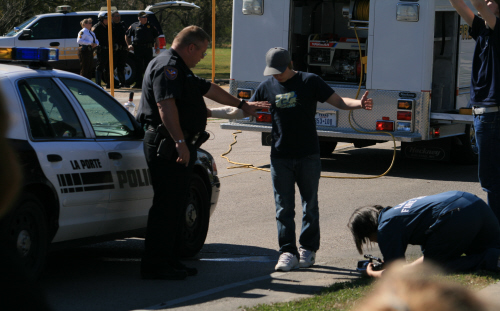 A young man performing a DUI test on the side of the road with a police officer