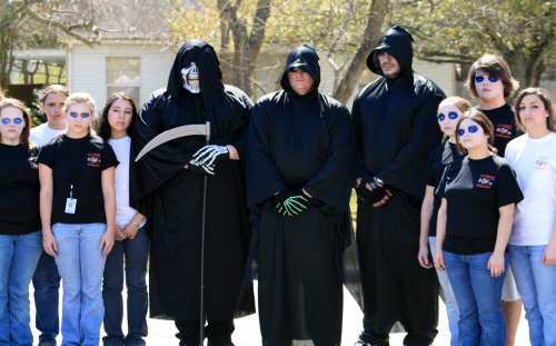 3 men in black trench coats with hoods surrounded by teens with face makeup on