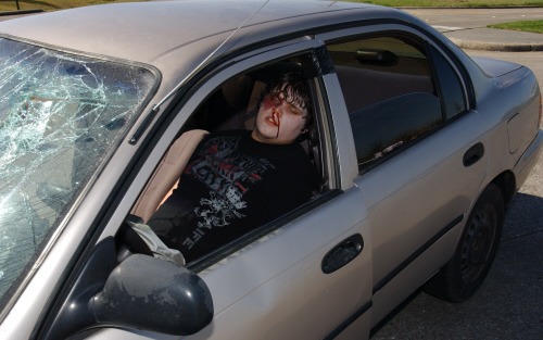 A boy with blood on his face in a gold car that was in a car crash