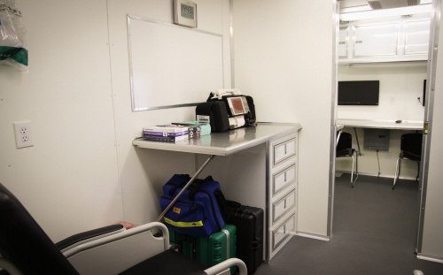 The desk area inside the Special Operations trailer with drawers, a white board and a monitor